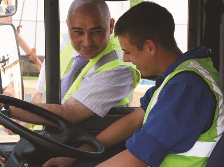 A LGV learner driver sitting in a lorry cab with an instructor showing him what to do